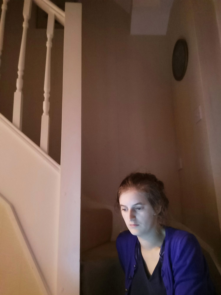 Sat on the bottom step of the stairs with my face lit by the light of my laptop