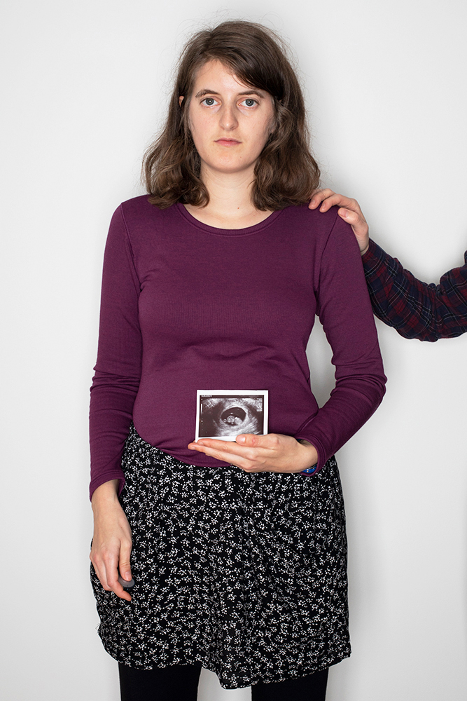 Me holding a scan of B when I was 9 and a half weeks pregnant. T has his right hand on my left shoulder.